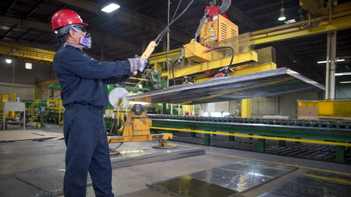 An employee uses an overhead crane to move a large lead metal plate at Seafab Metals' Casa Grande facility.