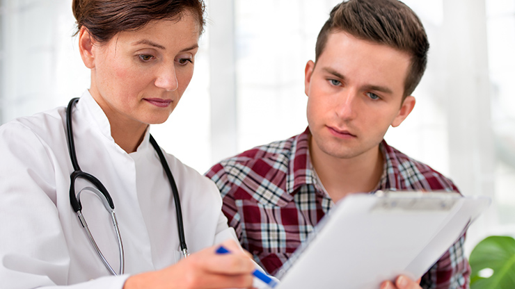 Physician and patient reviewing documents together.