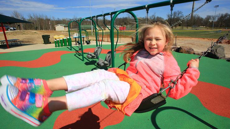 Child swinging at the all-abilities Kade's Playground in Herculaneum, Missouri.