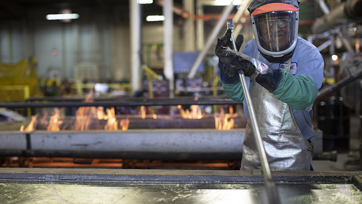 An employee skims dross off hot, liquid lead as a part of the metal refining process.