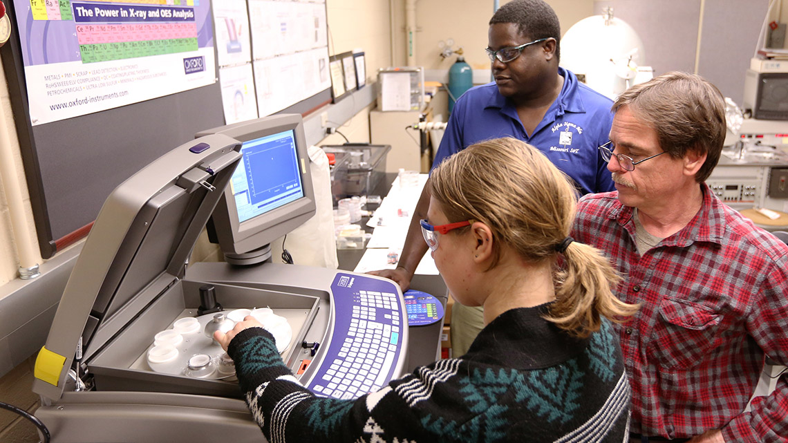 Missouri S&T professor and students using the X-ray fluorescence spectrometer Doe Run purchased for the university.