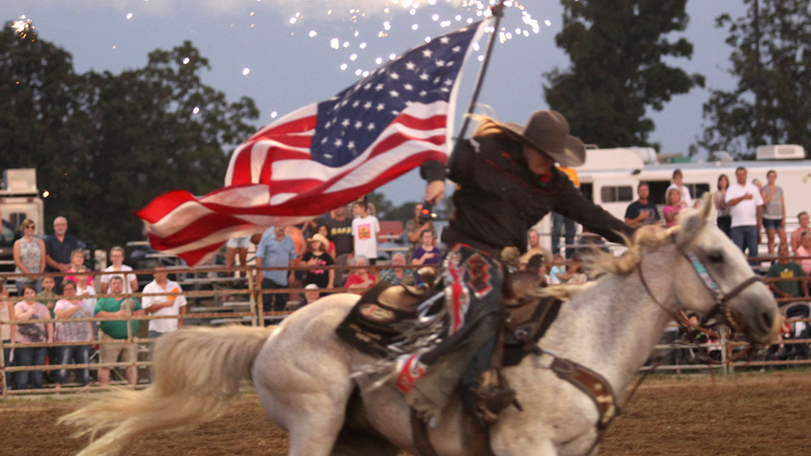 Woman on horseback carrying an American flag at the Salem, Missouri, Rodeo. Photo credit: Donald Dodd, The Salem News