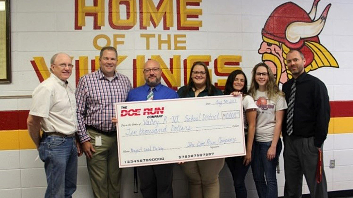 Doe Run employees present a $10,000 check to teachers and administrators of the Valley R-VI School District.