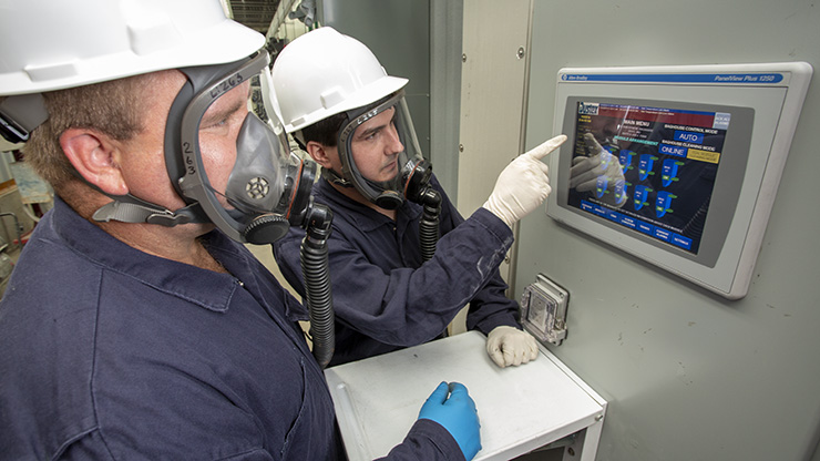 Two Resource Recycling employees check baghouse operational monitors.