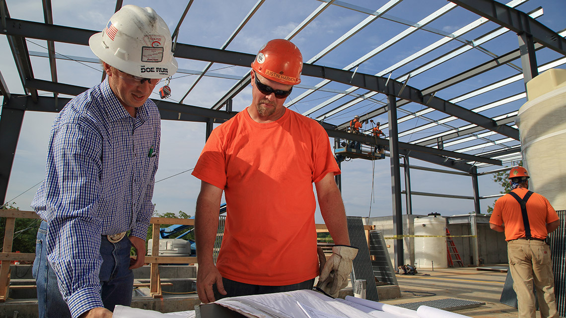 Doe Run employee and construction worker reviewing blueprints for a water treatment plant.