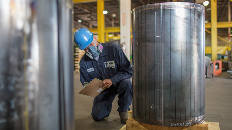 A Seafab Metals Company employee inspects a lead-lined nuclear cask.