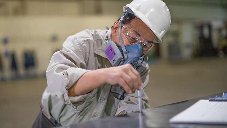 A Seafab Metals Company employee measures the thickness of a lead metal sheet to ensure it meets exacting standards.