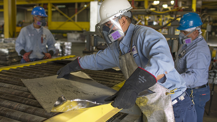 Seafab Metals Company employees pull finished, rolled lead metal from the rolling mill.