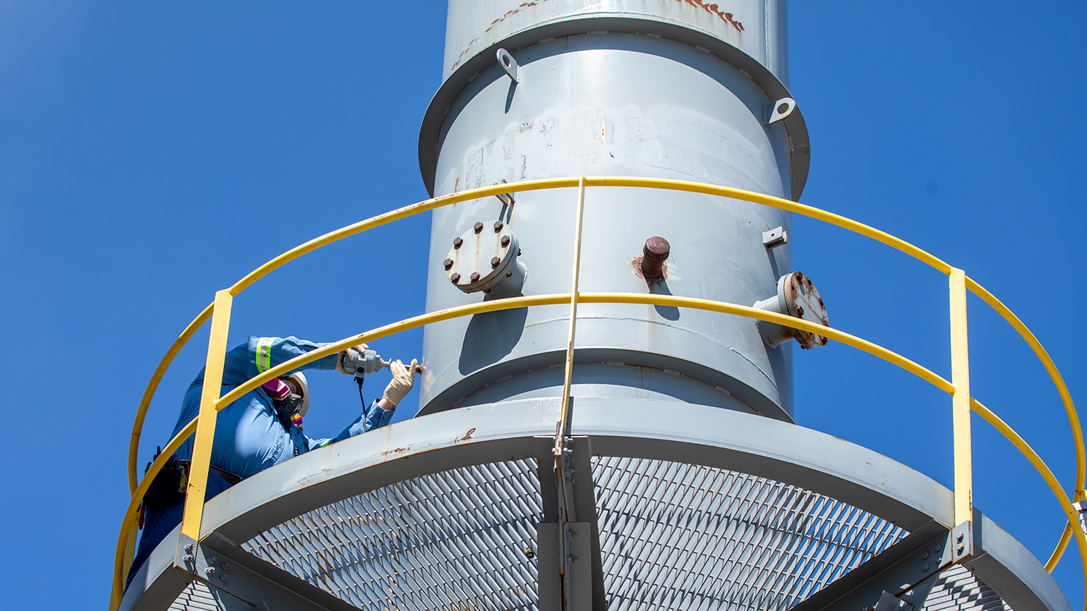 An employee is using a probe to evaluate air emissions from a stack.